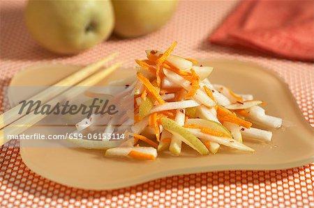 Poire asiatique et salade de carottes râpées sur une plaque. Baguettes