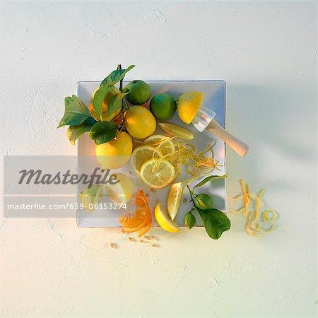 Zitronen und Limetten mit Blättern auf einer quadratischen Platte