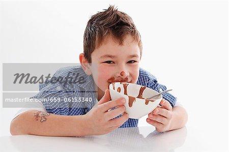 Small boy eating chocolate pudding