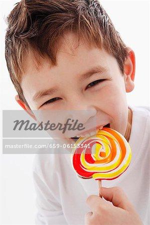 Un petit garçon de mordre dans une sucette