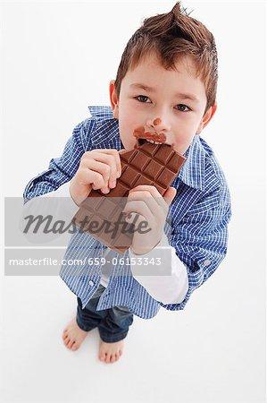 A little boy eating a bar of chocolate