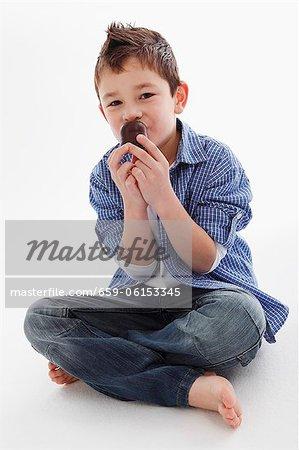 Un petit garçon manger une guimauve au chocolat