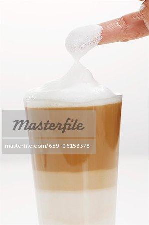 Milchschaum bedeckt Finger aus dem Glas Latte Macchiato
