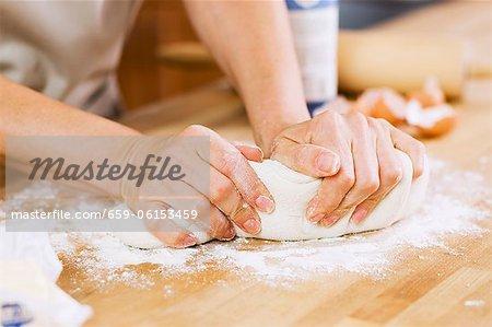 Frau kneten Teig auf einem bemehlten Counter in Küche