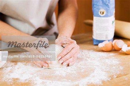 Frau vorbereiten Teig auf einer bemehlten Fläche in Küche