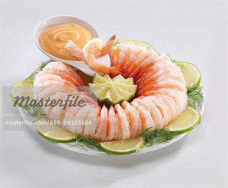 Anneau de crevettes avec sauce cocktail, limes et dill