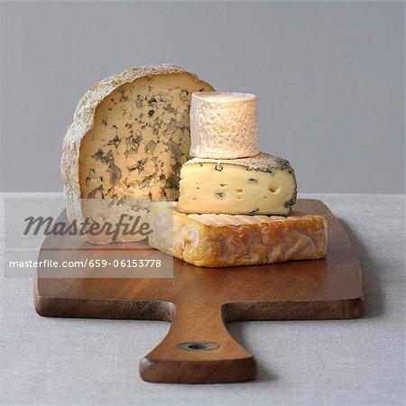 Quatre variétés de fromage sur une planche de bois