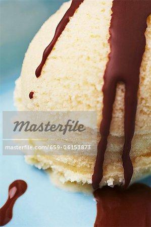 A scoop of vanilla ice cream with chocolate sauce (close-up)