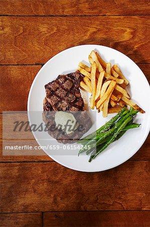 Steak grillé avec des frites et des haricots verts sur une assiette blanche ; D'en haut
