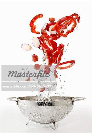 Poivrons, des tomates et des radis, lavés dans une passoire