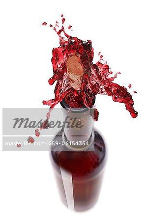 Spritzen aus einer Flasche Rotwein