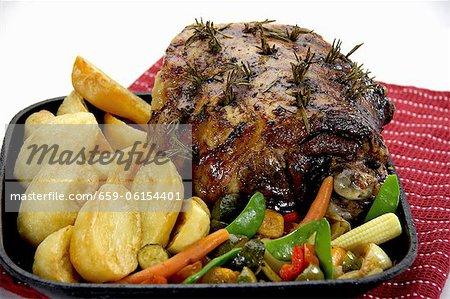 Rôti de gigot d'agneau au romarin, pommes de terre et légumes