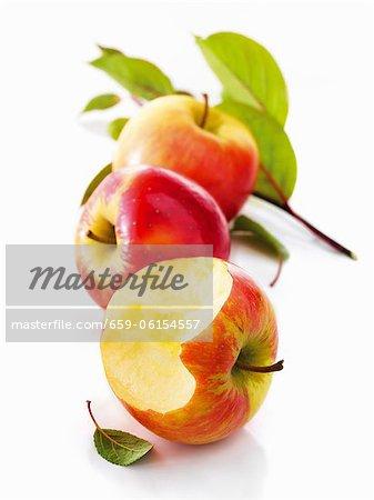 Pommes rouges, avec une morsure prise hors de lui, avec des feuilles