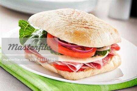 Salami und Käse-Sandwich mit Salat, Tomaten und Zwiebeln auf Ciabatta-Brot