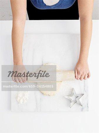 Eine Frau auf einer Marblew Arbeitsfläche heraus Teig Rollen