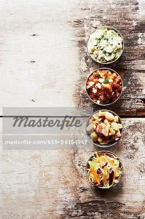 Plats d'accompagnement barbecue dans des petits bols sur une Table en bois ; Porc et haricots, salade de pommes de terre, salade de chou et Succotash