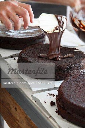 A chocolate cake being glazed