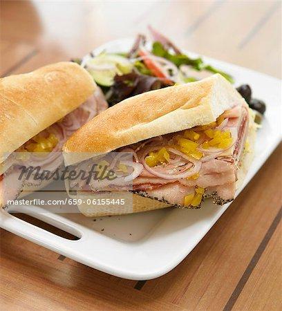 Italienisch-Sandwich; Aufschnitt mit Zwiebeln und Peperoni auf Baguette
