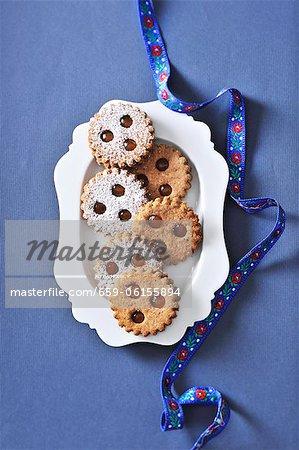 Linzer Augen (nussig Mürbeteig Marmelade Sandwich Kekse mit Löchern oben) auf einem Teller servieren