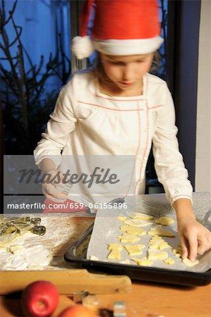 Ein Mädchen ausgeschnitten Kekse auf einem Backblech platzieren