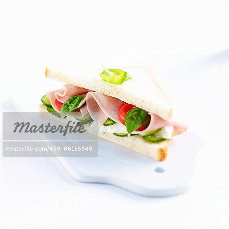 A ham, Camembert, tomato, cucumber and basil sandwich