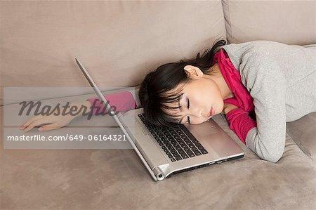 Frau schlafen auf Laptop auf couch