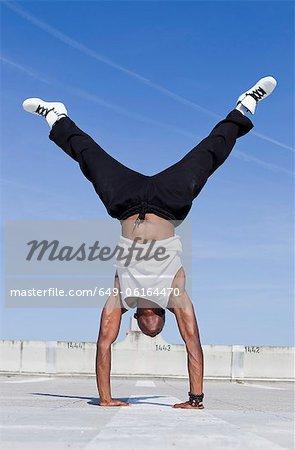 Man doing handstand on urban rooftop