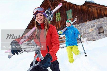Skifahrer tragen der Skier und Stöcke im Schnee
