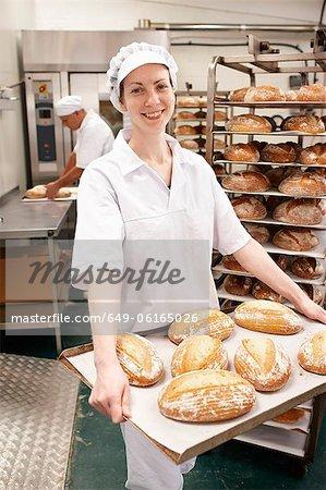 Chef portant plateau de pain dans la cuisine
