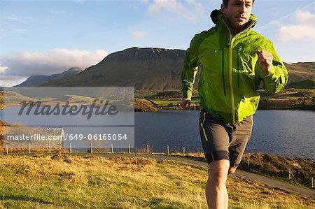 Wanderer grasbewachsenen Hang hinauf laufen