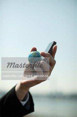 Unternehmer holding Globus Kugel und Handy