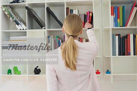 Frau ein Buch aus Regal nehmen