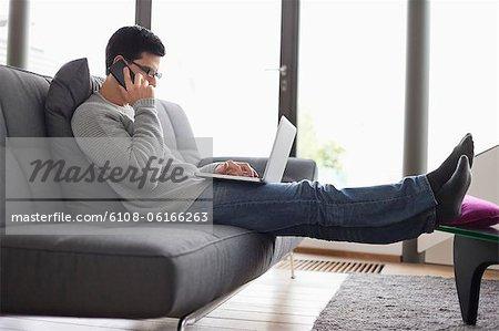Homme de parler sur un téléphone mobile tout en utilisant un ordinateur portable