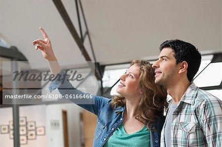 Femme heureuse pointant avec son mari à côté d'elle