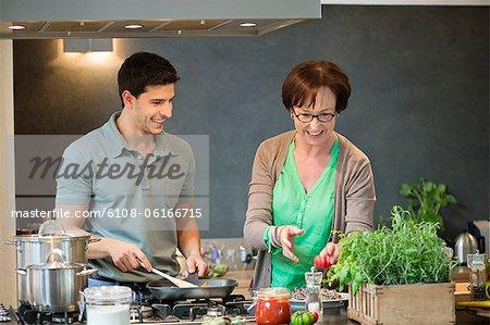 Femme aide son fils pour cuire les aliments dans la cuisine