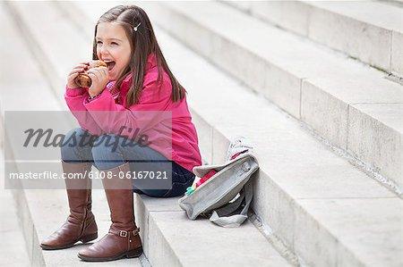 Schulmädchen auf der Treppe sitzen und Essen Pain au chocolat