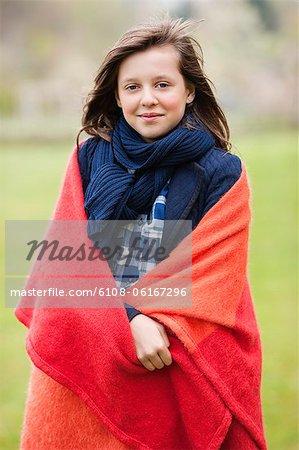 Portrait d'une jeune fille, enveloppé dans une couverture et souriant