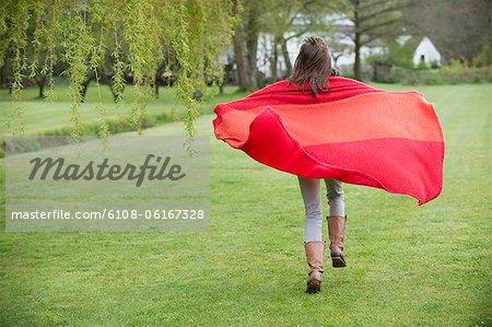 Fille en cours d'exécution dans un champ avec une couverture