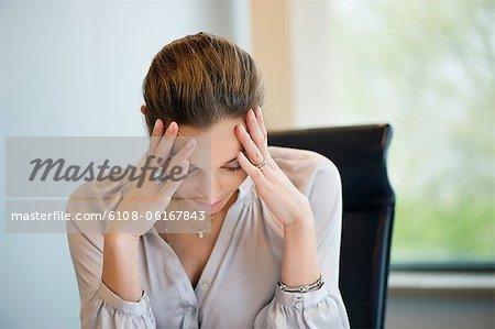 Gros plan d'une femme souffrant d'un mal de tête dans un bureau