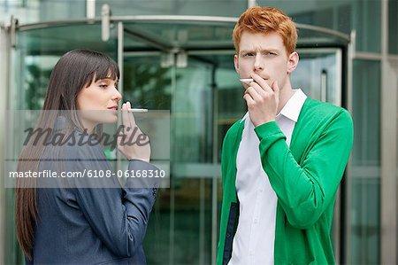 Dirigeants d'entreprises fumer devant un immeuble de bureaux