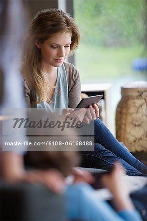 Frau elektronisches Buch lesen, mit ihren Kindern zu Hause