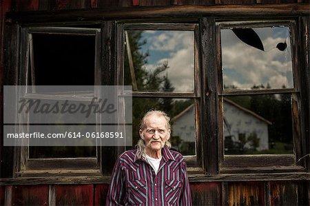 Senior man outside shack, portrait