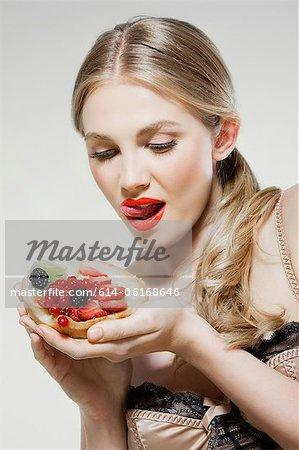 Young woman eating fresh fruit tart