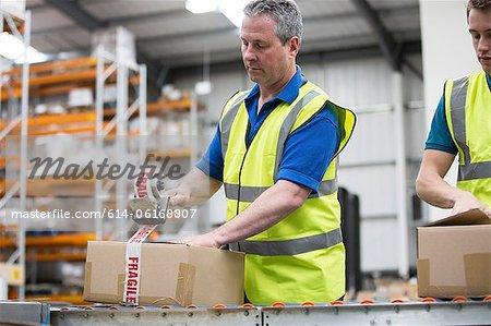 Men packing cardboard box in warehouse