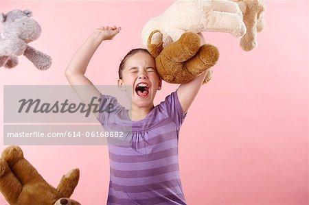 Jeune fille jetant des ours en peluche