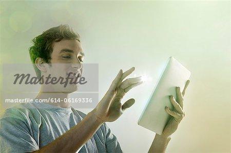 Jeune homme à l'aide de la tablette numérique avec lumières
