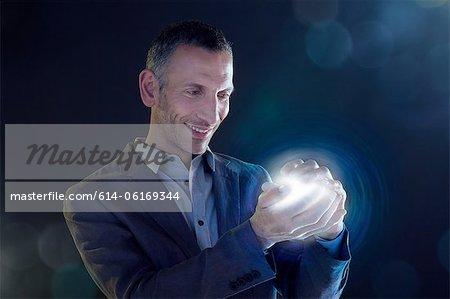 Businessman holding a ball of light