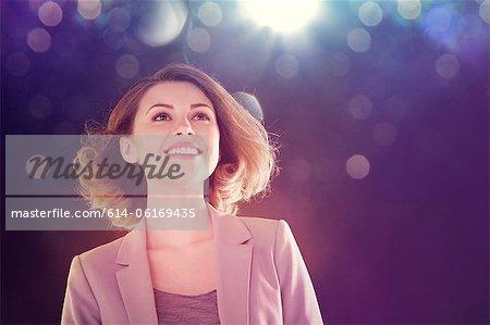 Jeune femme regardant vers le haut de lumières