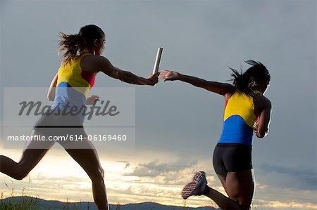 Female relay racers passing baton