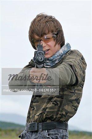 Boy Pointing Rifle at Camera